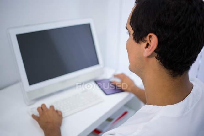 Visão traseira do dentista usando o computador na clínica — Fotografia de Stock