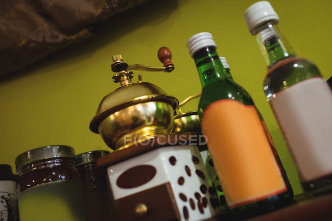 Close-up of coffee grinder and syrup bottles arranged on shelf in shop — Stock Photo