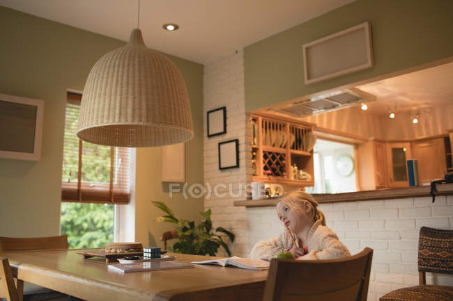 Thoughtful girl sitting at table and studying at home — Stock Photo