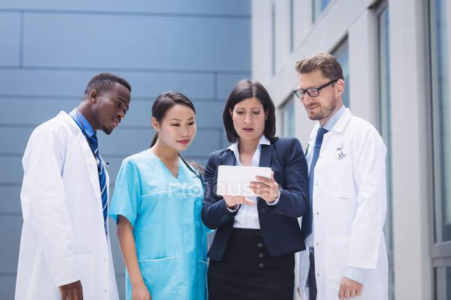 Équipe de médecins regardant la tablette numérique dans les locaux de l'hôpital — Photo de stock