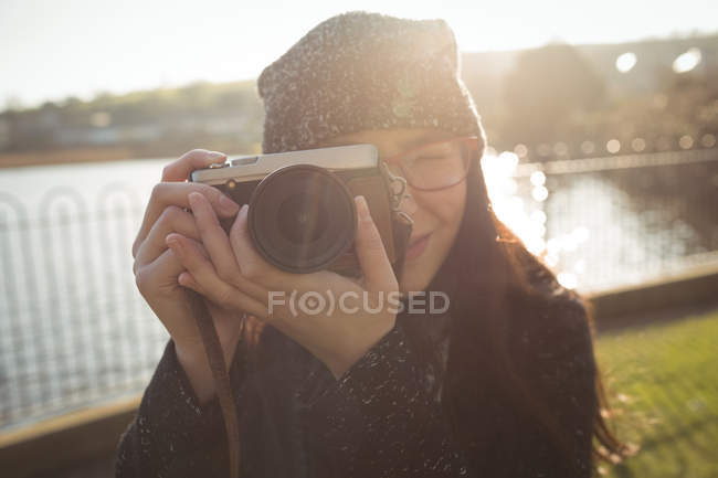 Woman taking photos on digital camera on a sunny day in park — Stock Photo
