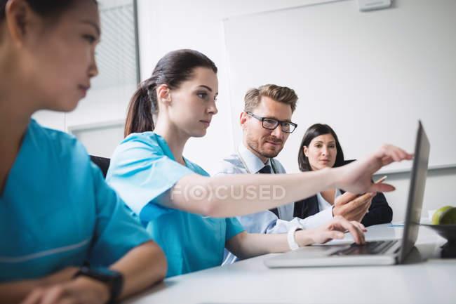 Врачи обсуждают за ноутбуком в конференц-зале — стоковое фото