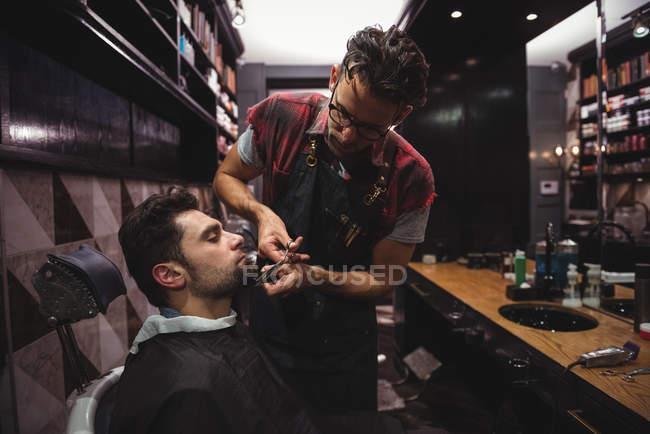 Uomo ottenere barba tagliata da parrucchiere con le forbici in negozio di barbiere — Foto stock