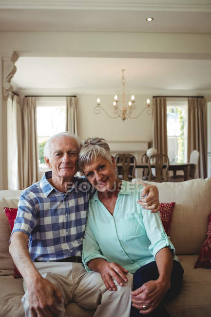 Portrait of senior couple relaxing on sofa in living room at home — Stock Photo