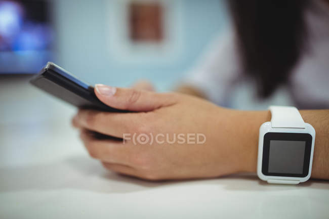Hands of businesswoman using mobile phone in office — Stock Photo