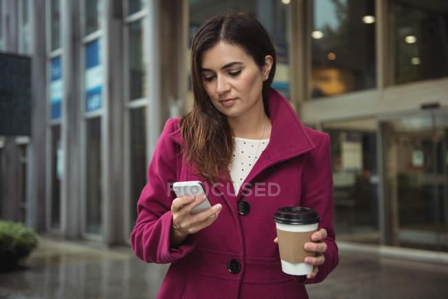 Femme d'affaires tenant tasse de café jetable et en utilisant le téléphone mobile dans la rue — Photo de stock