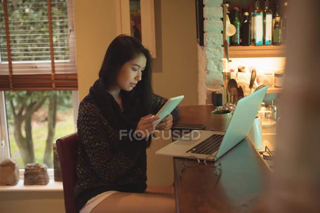 Frau nutzt digitales Tablet am Küchentisch in der Wohnung — Stockfoto