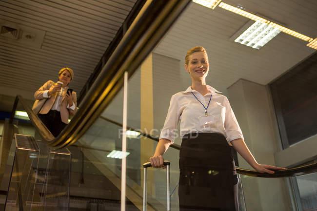 Retrato del personal femenino bajando de la escalera mecánica en la terminal del aeropuerto - foto de stock