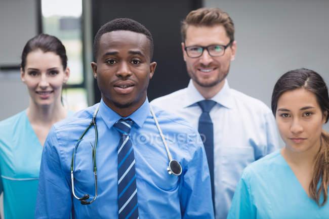 Retrato de la sonrisa permanente de equipo médico en pasillo de hospital - foto de stock