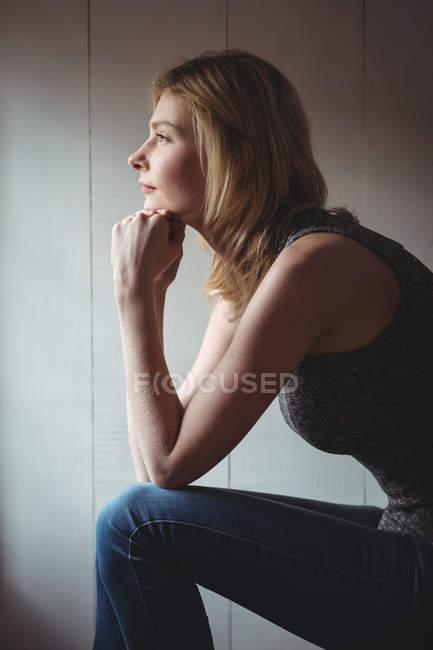 Продуманий жінка, що сидить з боку на підборідді вдома — стокове фото