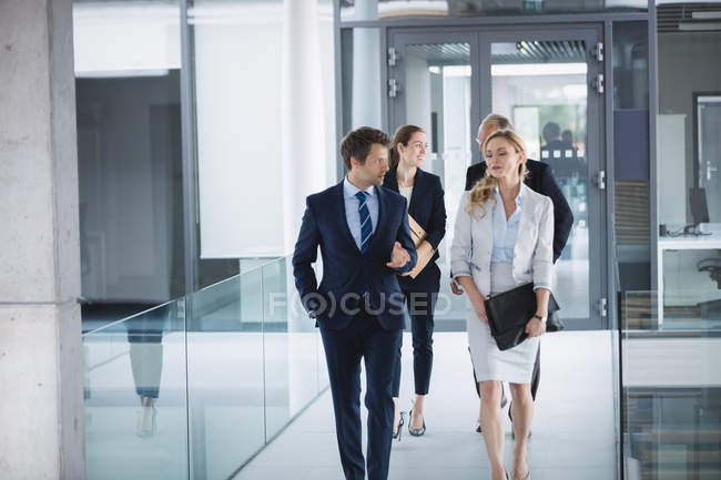 Fiducioso uomo d'affari che cammina con i colleghi all'interno dell'edificio per uffici — Foto stock