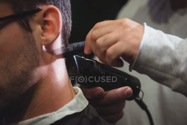Primo piano di uomo ottenere capelli tagliati con trimmer in negozio di barbiere — Foto stock
