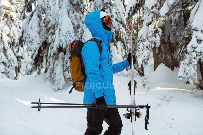 Side view of skier walking with ski on snow covered mountains — Fotografia de Stock