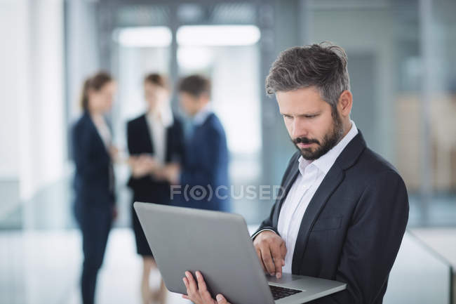 Businessman standing in office and using laptop — Stock Photo