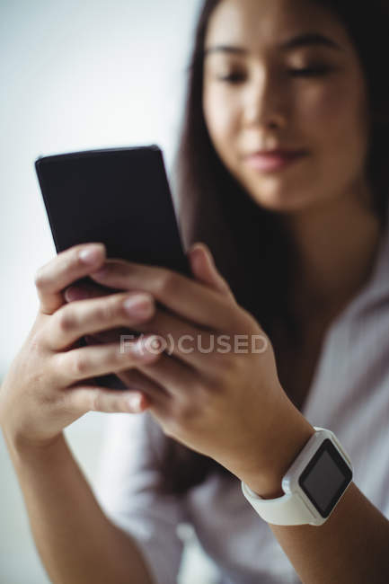 Businesswoman using mobile phone in office — Stock Photo