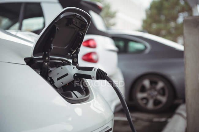 Close-up of car being charged with electric car charger at charging station — Stock Photo
