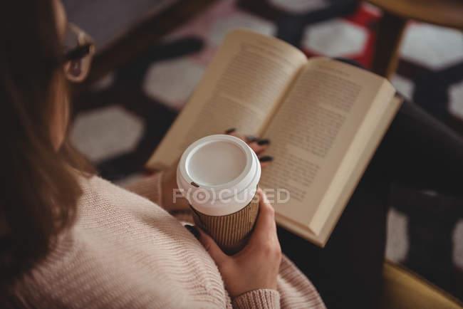 Frau liest Buch, während sie zu Hause Kaffee trinkt — Stockfoto