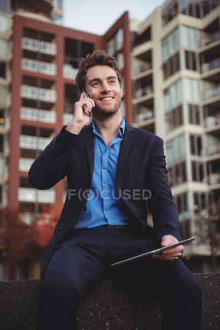 Homme d'affaires parlant sur un téléphone portable et tenant une tablette numérique près d'un immeuble de bureaux — Photo de stock