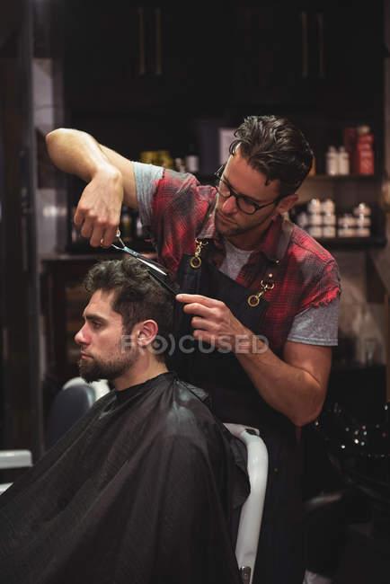 Uomo ottenere capelli tagliati dal parrucchiere con le forbici in negozio di barbiere — Foto stock