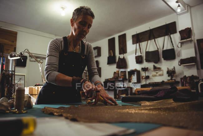 Atento artesão corte de couro na oficina — Fotografia de Stock