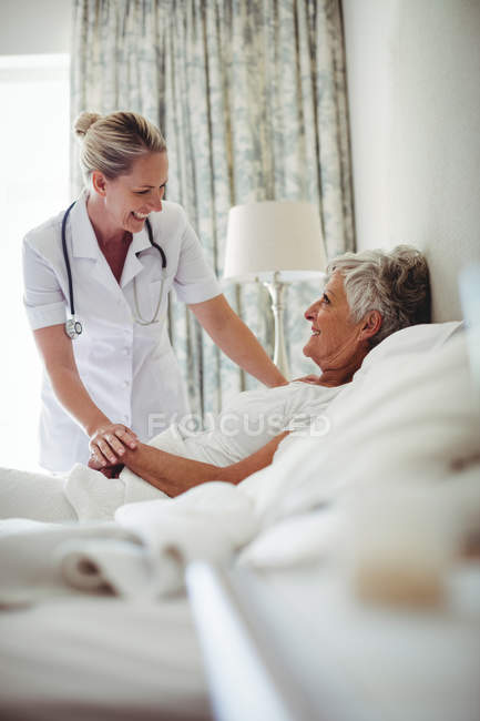 Female doctor interacting with senior patient at home — Stock Photo
