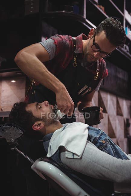 Barbiere applicando crema su barba di cliente in negozio di barbiere — Foto stock