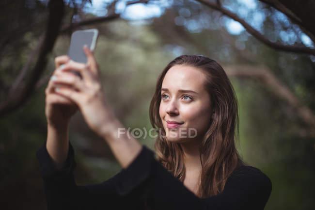 Belle femme prenant selfie sur téléphone mobile en forêt — Photo de stock