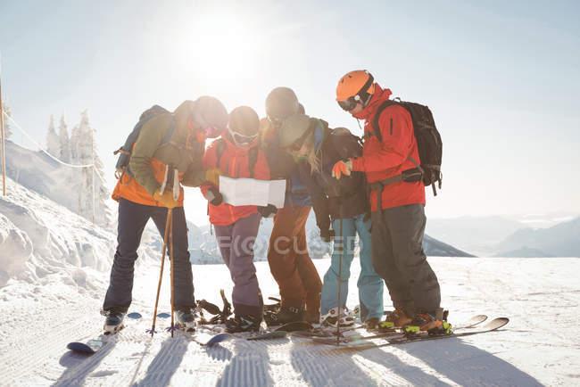 Группа лыжников зимой смотрит на карту в снежных Альпах — стоковое фото