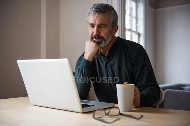 Man looking at laptop while having a cup of coffee at home — Stock Photo