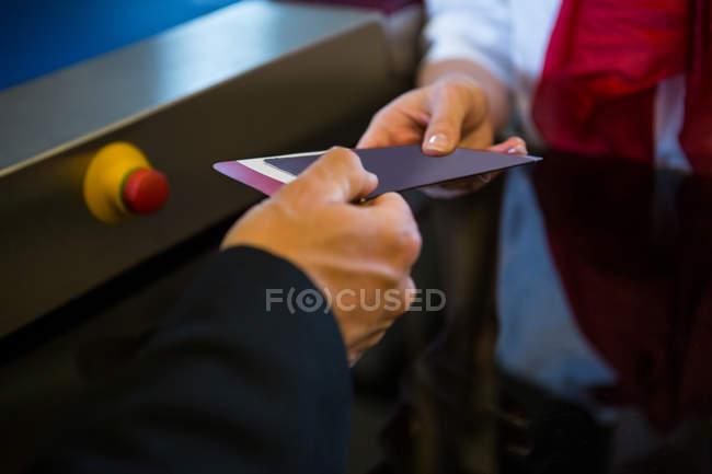 Personal femenino dando la tarjeta de embarque para el empresario en el check-in desk - foto de stock