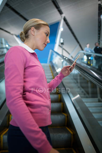 Female commuter using mobile phone on escalator in airport — Stock Photo