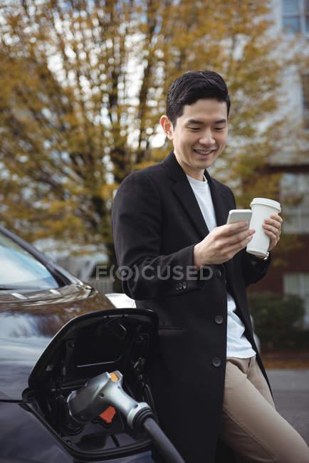 Homme à l'aide de téléphone portable pendant le chargement de voiture à charge conductive pour véhicules électriques — Photo de stock