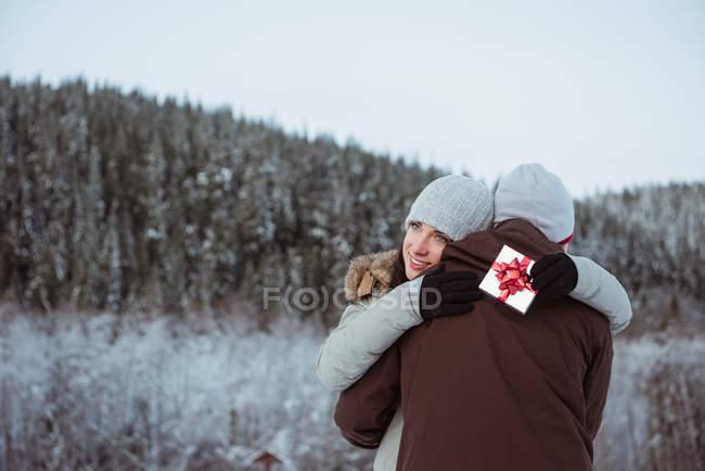 Pareja feliz abrazándose en la montaña cubierta de nieve - foto de stock