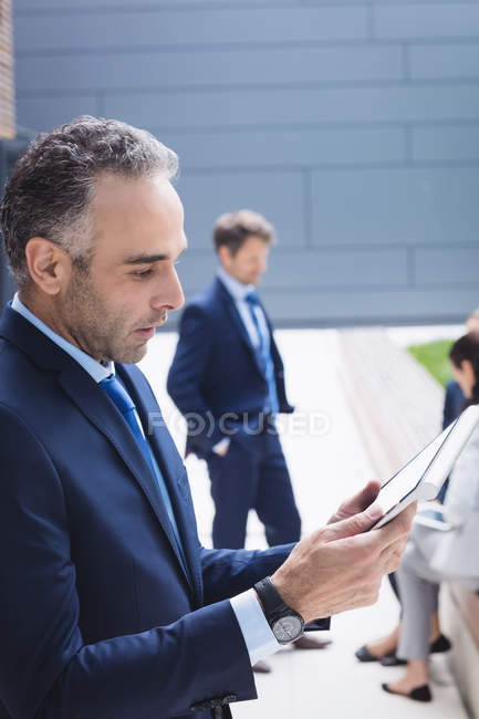 Businessman using digital tablet outside office building — Stock Photo
