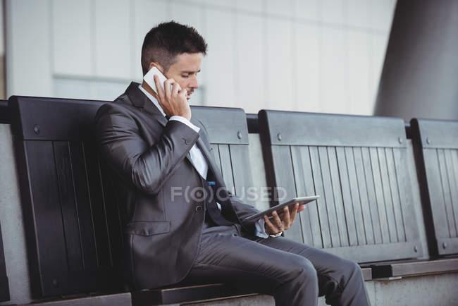 Empresario que usa tableta digital mientras habla por teléfono móvil en el campus de la oficina - foto de stock