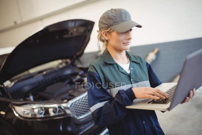 Жіночий механік, використовуючи ноутбук у ремонт гаража — стокове фото