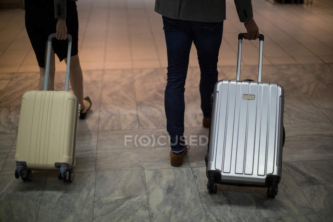 Business people walking with luggage at airport terminal — Stock Photo