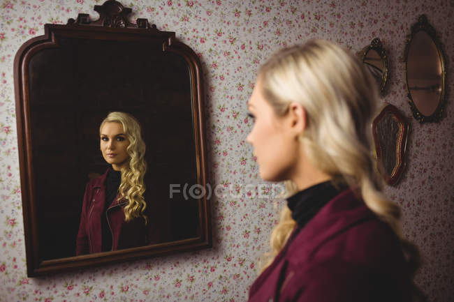 Beautiful woman standing in front of mirror — Stock Photo
