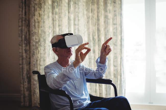 Homem sênior sentado em cadeira de rodas e usando fone de ouvido realidade virtual no quarto em casa — Fotografia de Stock
