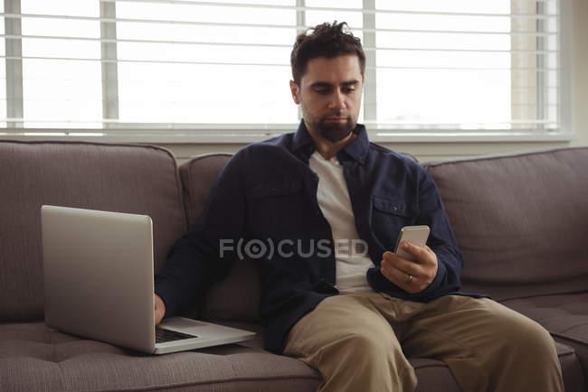 Uomo che utilizza telefono cellulare e laptop sul divano di casa — Foto stock
