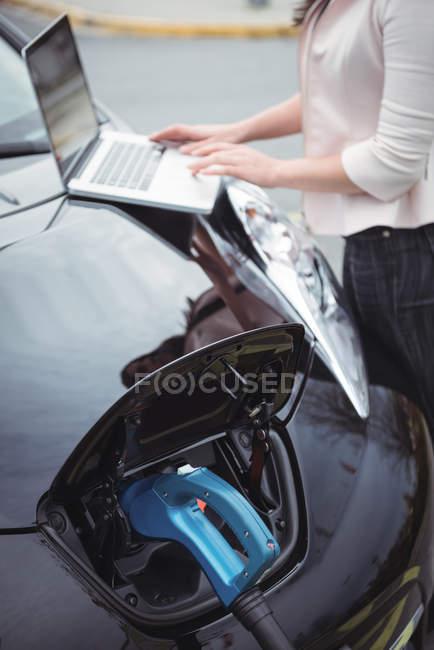 Partie médiane de la femme en utilisant un ordinateur portable tout en chargeant la voiture électrique sur la rue — Photo de stock