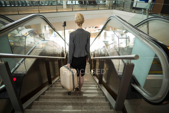 Rear view of business woman standing on escalator with luggage at airport — Stock Photo