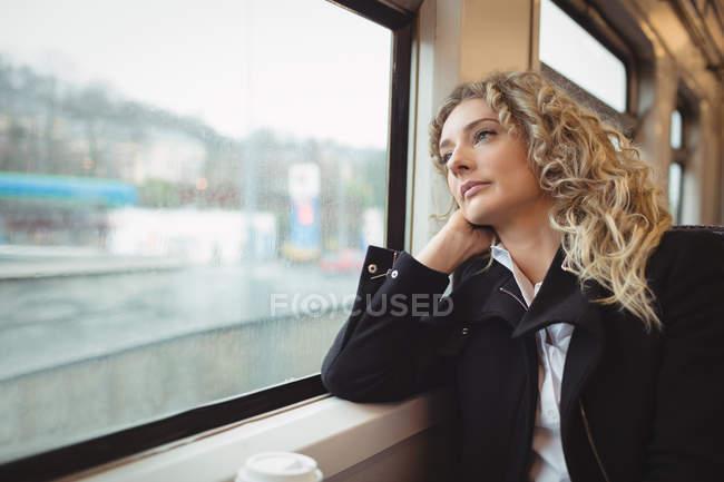 Задумчивая деловая женщина смотрит в окно во время путешествия — стоковое фото