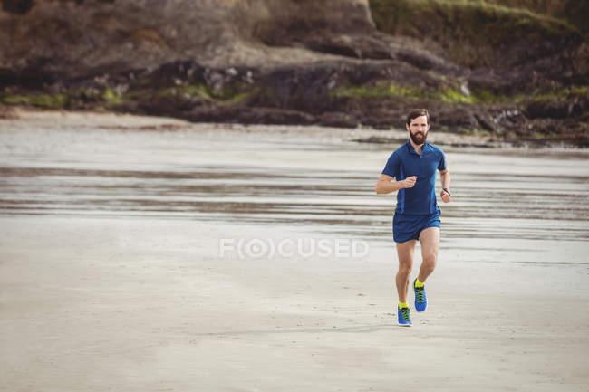 Schöner Athlet läuft am Sandstrand — Stockfoto