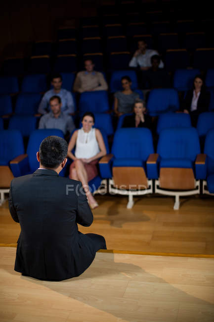 Rear view of male business executive talking to colleagues at conference center — Stock Photo