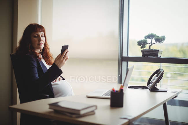 Pregnant businesswoman using mobile phone in office — Stock Photo