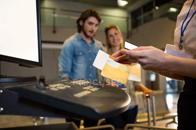 Personal del aeropuerto mujer con teléfono móvil para escanear el pasaporte en el aeropuerto terminal - foto de stock