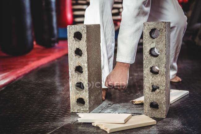 Каратист разбивает деревянную доску в фитнес-студии — стоковое фото