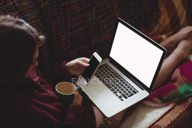 Donna che prende il caffè mentre usa il computer portatile e il telefono cellulare sul divano a casa — Foto stock