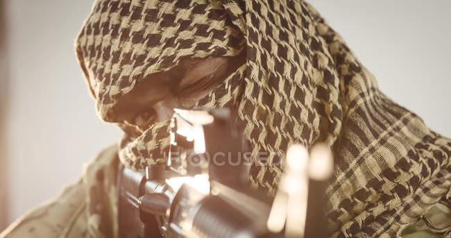 Close-up of terrorist aiming with machine gun — Stock Photo